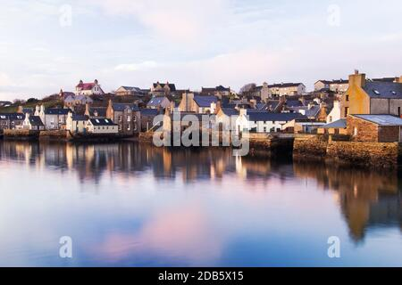 Morning light in waterfront view of Stromness harbour with white houses and reflections in water