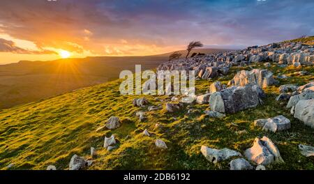 Dramatic sunset at Twistleton Scar in the Yorkshire Dales National Park with moody clouds.