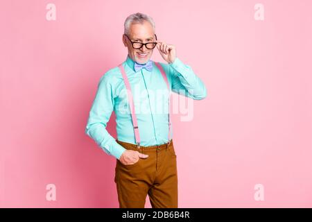 Photo portrait of happy smiling elder man touching eyeglasses wearing bright shirt bowtie suspenders brown trousers isolated on pink color background