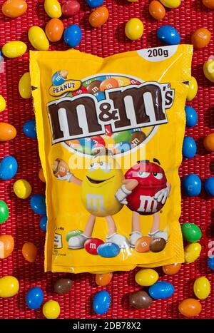 M&Ms retail Packaging with loose colorful candy in a flat lay still life on a red textile background