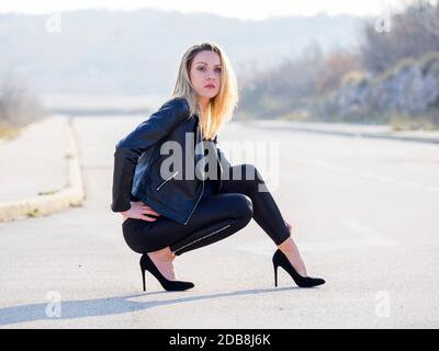 Attractive slim young woman slender fit slenderfit thin is kneeling squatting on road legs heels eyeshot eyes eye contact looking at camera profile Stock Photo