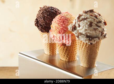Three ice cream cones with assorted flavors including chocolate, strawberry and choc chip standing in a metal holder on a counter Stock Photo