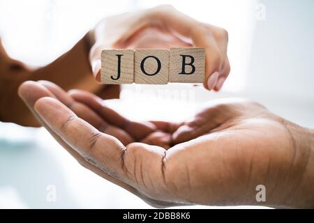 Close-up Of Businessperson's Hand Giving Wooden Block With Job Text To Candidate Stock Photo