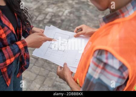 close up of male and female Asian contractors holding the building site plan during building construction