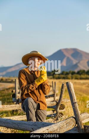 USA, Idaho, Bellevue, Rancher standing by fence and putting on gloves