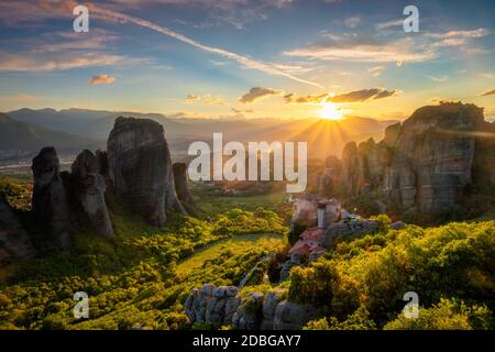 Sunset over monastery of Rousanou and Monastery of St. Nicholas Anapavsa in famous greek tourist destination Meteora in Greece on sunset with sun rays