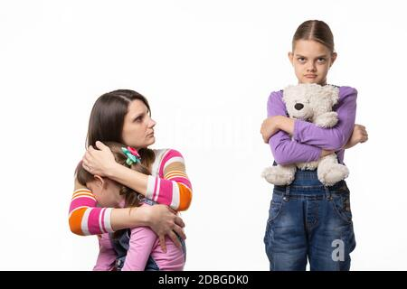 Mom reproachfully looks at the eldest daughter for offending the younger daughter - Stock Photo