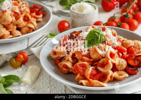 South italian  pasta orecchiette with tomato sauce and cacioricotta cheese close up - Stock Photo