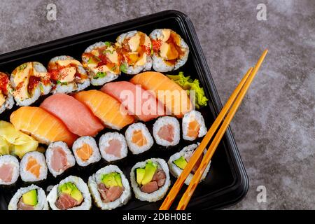 Assortment of sushi roll set on a black tray. Japanese food. Top view.