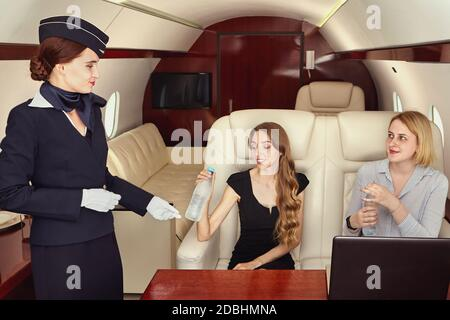 Cabin crew serves business class passengers inside the plane. Air hostess is serving female-passenger in the private jet.