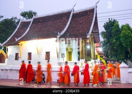 Buddhist monks receive rice from locals during an early morning daily ritual known as Sai Bat (morning alms) in Luang Prabang, Laos
