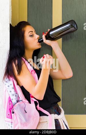 Schoolgirl school-girl teengirl is drinking alcohol standing inclined on wall - Stock Photo