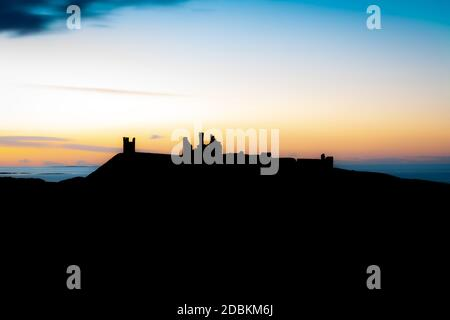 A late summer night in Northumberland looking North over Dunstanburgh Castle. - Stock Photo