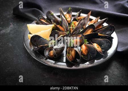 Mussels with lemon and parsley on a plate with a dark napkin on a black slate table, selected focus, very narrow depth of field