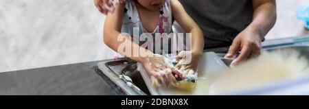 Panoramic web banner of asian girl washing dish and tableware with her mom, housework for child make executive function for kid. Houseworking for kid