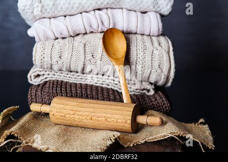 Wooden rolling pin and spoon on desk and piles of sweaters in the background at home. Copy space for design or text