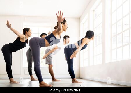 Group of sporty attractive asian people wearing sportswear bra pants practicing yoga lesson on Uttanasana pose Standing Forward Bend with instructor c