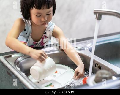 Asian girl washing her dish and tableware by herself, housework for child make executive function for kid. House-working for kid lifestyle and family