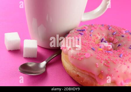 A closeup of a pink frosted donut and coffee for a quick break. - Stock Photo