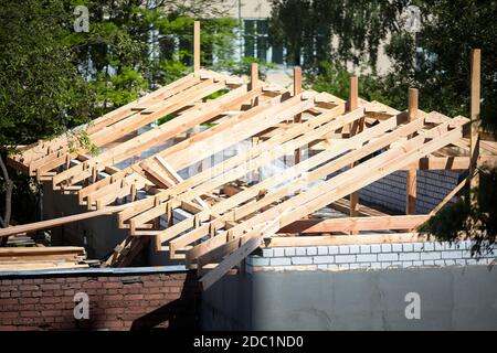 Roofing construction with wooden beams, logs, rafters, trusses. Roof structure on top of brick walls with plaster surrounded by foliage on sunny