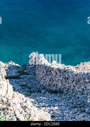 Drywall on Krk island near Voz, in Croatia Europe sunshine sunlight landscape scenery scenic view steep downwards towards sea calm dark Blue surface - Stock Photo