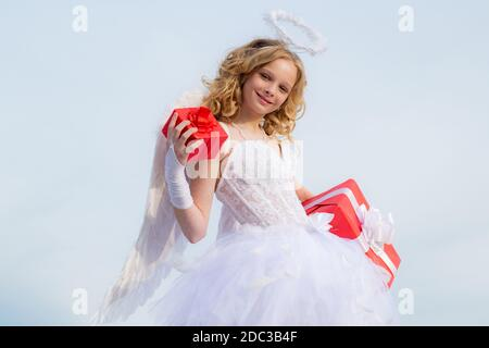Toddler girl wearing angel costume white dress and feather wings. Cute little Cupid angel with gift. Festive Art Greeting Card. - Stock Photo
