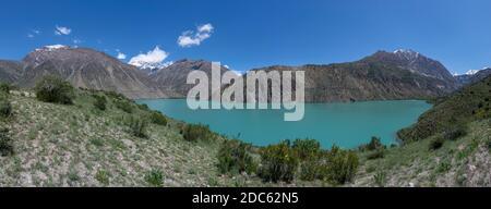 Panorama of the blue green Iskanderkul lake in Tazjikistan with high snowy mountains. - Stock Photo
