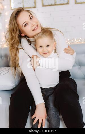 Happy blond hadsome boy and pretty woman enjoying Christmas Time and hugging Stock Photo