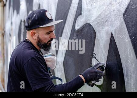 Graffiti artist in action, painting on the wall with aerosol spray paint in a can, wearing protective gloves. Street art culture concept. - Stock Photo