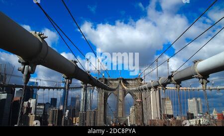walking the Brooklyn Bridge under blue sky and clouds