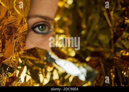 Green eye of a woman wearing makeup and wrapped in gold foil