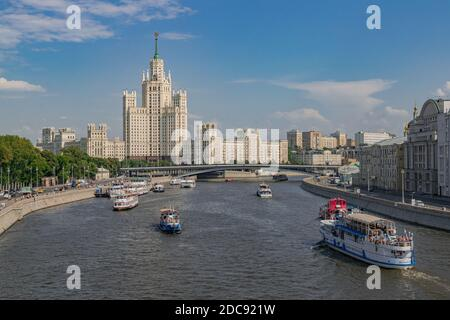 Moscow/Russia; June 22 2019: tourist boats on the Moscova River, with the Kotelnicheskaya Embankment Building in the background, in a summer day - Stock Photo