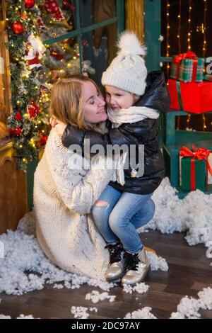 Blond woman and her little daughter hugging indoors Stock Photo