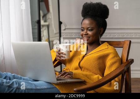 Happy Afro-American millennial woman with afro hairstyle wear yellow cardigan resting, sitting on chair, watching webinar, working online on laptop, t