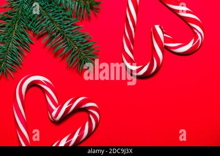Lollipop hearts on red surface with Christmas tree branches. Christmas and New Year greeting card