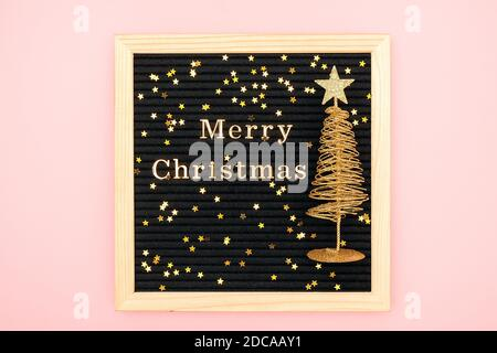 Letter board with golden text Merry Christmas, shiny christmas tree and confetti stars on pink background. Greeting card, postcard. Festive concept. - Stock Photo