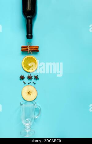 Mulled Wine Ingredients, still life on blue background. Bottle of wine, cinnamon sticks, slices of orange, apple, anise and mug. Concept culinary reci Stock Photo