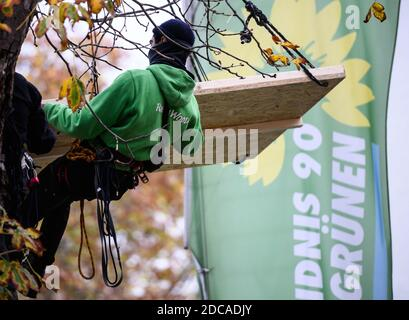 Wiesbaden, Germany. 20th Nov, 2020. An activist floats in front of the flag of Bündnis90/Die Grünen. Activists from Robin Wood, environmental and nature conservation organisation, have occupied two trees in front of the party headquarters of the Hessian Greens in the state capital. The organisation is protesting against the clearings in connection with the expansion of the A49 and wants to remind the Greens in Hesse of their political responsibility. Credit: Andreas Arnold/dpa/Alamy Live News - Stock Photo