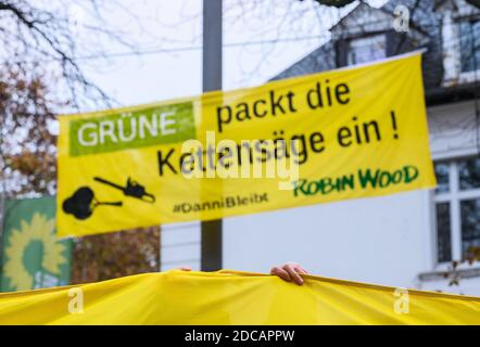 Wiesbaden, Germany. 20th Nov, 2020. An activist stands in front of a demo banner 'Green packs the chainsaw! #Danni stays Robin Wood'. Activists of Robin Wood, environmental and nature conservation organisation, have occupied two trees in front of the party headquarters of the Hessian Greens in the state capital. The organisation is protesting against the clearings in connection with the expansion of the A49 and wants to remind the Greens in Hesse of their political responsibility. Credit: Andreas Arnold/dpa/Alamy Live News - Stock Photo