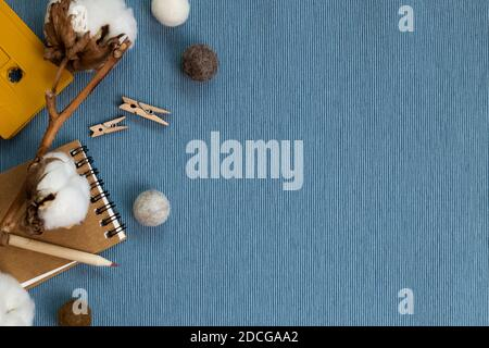 Winter concept. Notebook and pencil, cotton plant, cassette tape on blue fabric background. flat lay, top view, copy space. Work and study place - Stock Photo