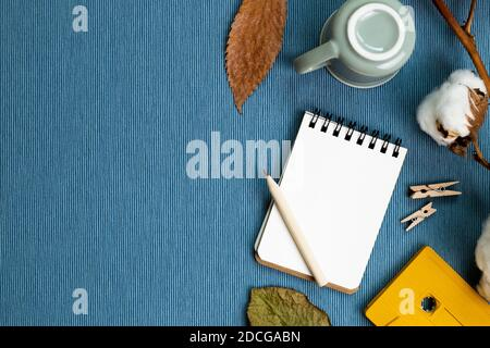 Work and study place. Winter concept. Notebook and pencil, mug cup, dry plant on blue fabric background. flat lay, top view, copy space - Stock Photo