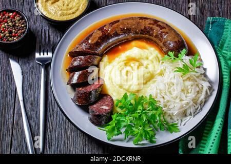 German food: blutwurst or blood sausage served on a plate with sauerkraut, mashed potato parsley, mustard, and peppercorns on a dark wooden table, top Stock Photo