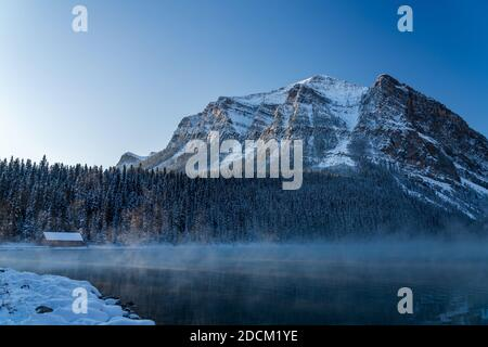 Lake Louise in early winter sunny day morning. Mist floating on turquoise color water surface. Clear blue sky, snow capped Fairview Mountain