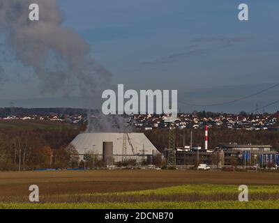 Steaming cooling tower of nuclear power plant operated by utility company EnBW with agricultural fields in front and village Neckarwestheim. - Stock Photo