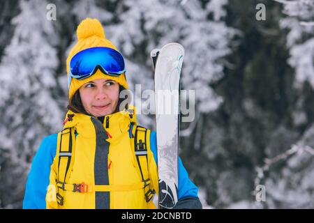 smiling stunning woman portrait in ski outfit winter activities - Stock Photo