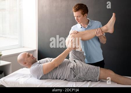 Serious physiotherapist holding patient leg while helping him with exercise