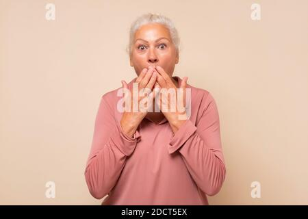 Senior shocked lady covering her mouth with palms being shocked with news - Stock Photo