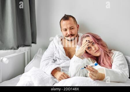 sick woman with husband on bed, female has high temperature, suffering from fever. in bedroom - Stock Photo