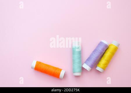 Colored sewing thread on a pink background