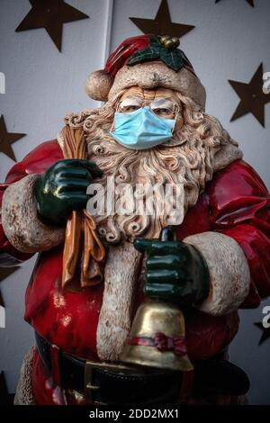 Delmenhorst, Germany. 23rd Nov, 2020. A Santa Claus was put on a protective mask. For months the Borchart family did handicrafts and decorations. Now their house is lit up right up to the top of the roof. Credit: Sina Schuldt/dpa/Alamy Live News - Stock Photo
